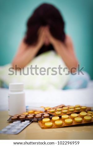 Medical tablets in the foreground with an out of focus woman in the background suffering from or depression or headache