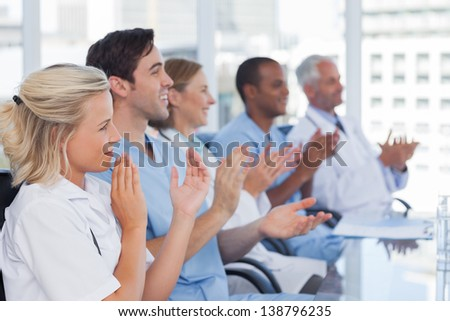 Medical team clapping hands during a conference - stock photo