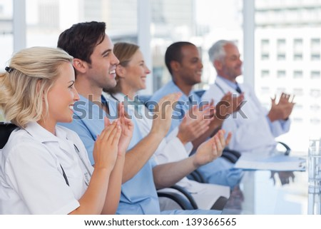 Medical team clapping  their hands during a meeting - stock photo