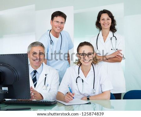 Medical team comprising male and female doctors posing together in an office smiling at the camera - stock photo