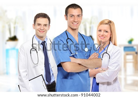 Medical team consisting of three smiling doctors inside a hospital - stock photo