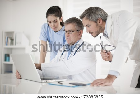 medical team discussing around a computer - stock photo