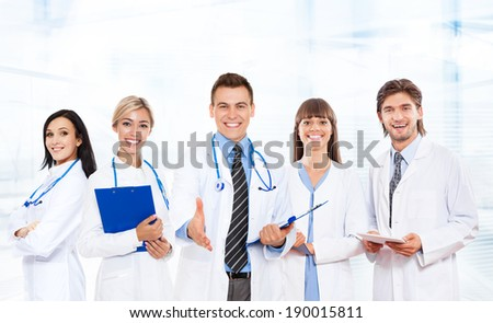 medical team doctor handshake, hold hand shake welcome gesture happy smile with group of people in hospital - stock photo