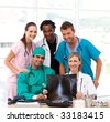 Medical team examining an X-ray in hospital and smiling at the camera - stock photo