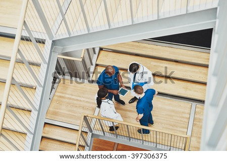 Medical team having an emergency discussion standing grouped in a stairwell at the hospital looking up information on a tablet,, view from above down the stairwell - stock photo