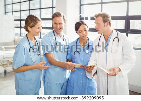 Medical team interacting with each other in hospital - stock photo