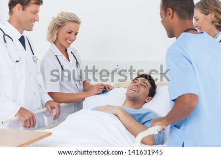 Medical team laughing with a patient - stock photo