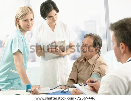 Medical team measuring blood pressure of senior patient, nurse assisting, doctors taking notes on clipboard.? - stock photo