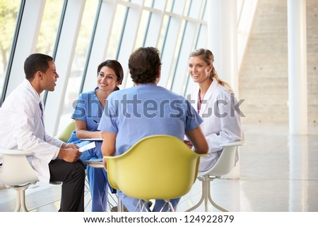 Medical Team Meeting Around Table In Modern Hospital - stock photo