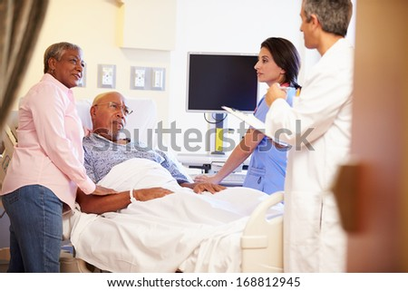 Medical Team Meeting With Senior Couple In Hospital Room - stock photo