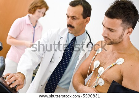 Medical team performing an EKG test on  young male patient. Real people, real location, not a staged photo with models. Focus is placed on the  patient. - stock photo