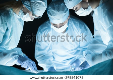 Medical team performing operation. Group of surgeon at work in operating theatre toned in blue - stock photo