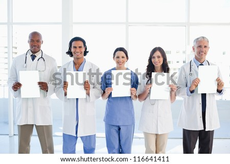 Medical team standing upright holding blank sheets in front of the bright window - stock photo
