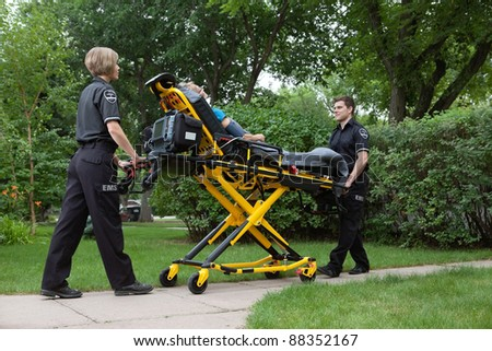 Medical team transporting patient on stretcher - stock photo