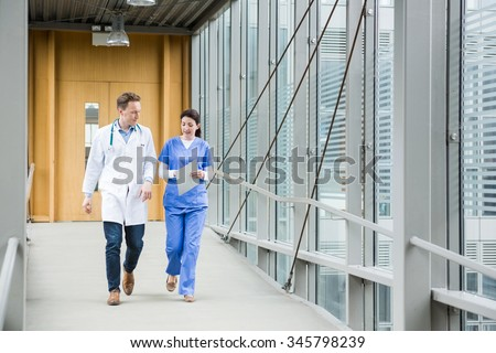 Medical team walking down hallway at the hospital - stock photo