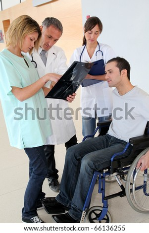 Medical team with handicapped person looking at X-ray - stock photo