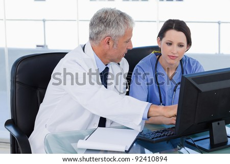 Medical team working together with a computer in an office - stock photo