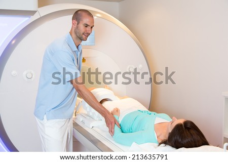 Medical technical assistant councelling patient and preparing scan of the knee with magnetic resonance tomography MRI in radiology - stock photo