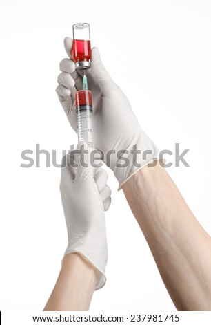 Medical theme: doctor's hand in a white glove holding a syringe and picking up of red liquid for injection ampules on a white background - stock photo