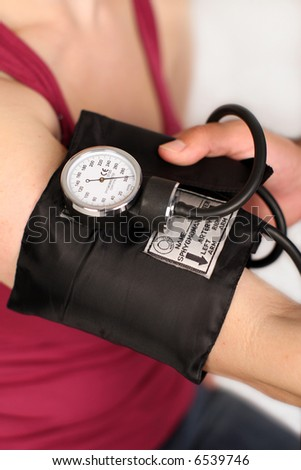 Medical worker checking woman's blood pressure - stock photo