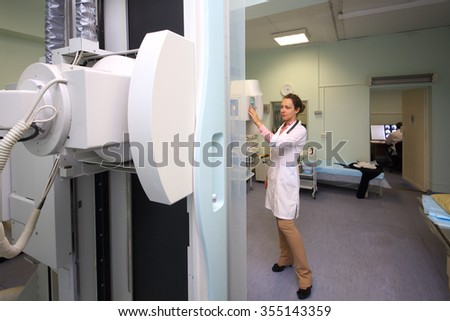 Medical worker controls x-ray equipment in hospital - stock photo