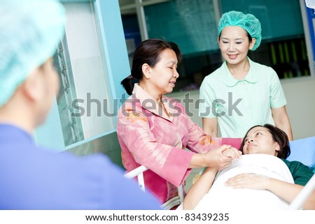 medical worker moving patient with her cousin on hospital trolley to operating room - stock photo