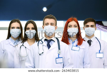 Medical workers in medical masks in conference room