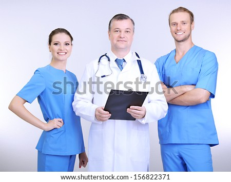 Medical workers on grey background - stock photo