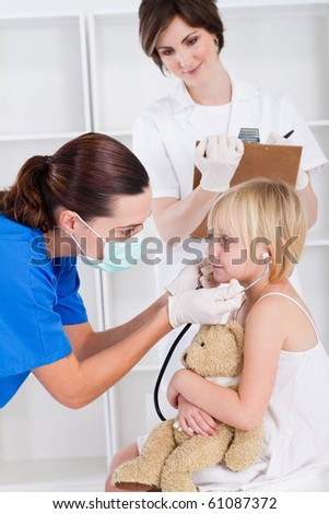 medical workers playing with little girl - stock photo