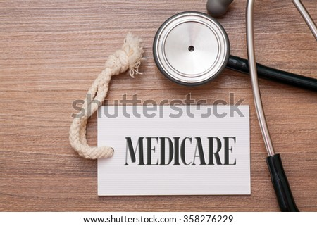 Medicare written on price tag sign and stethoscope. Medicine concept on wood background - stock photo