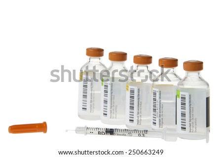 Medication bottles vials with injectable medication lined up in a row with a 40 unit per milliliter syringe lying in front with one drop of medication coming out of the tip of the needle. Cap on side - stock photo