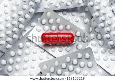 Medication. Giant red pill on smaller white pills in blister packs. - stock photo