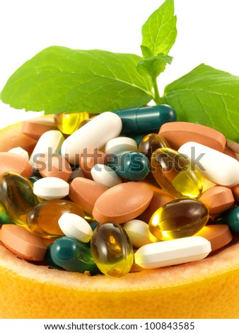 Medication in grapefruit bowl with leaf of mint - stock photo