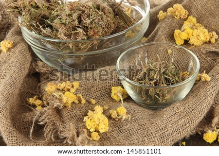 Medicinal Herbs in glass bowls on bagging close-up - stock photo