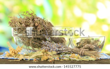 Medicinal Herbs in glass bowls on napkin on wooden table - stock photo