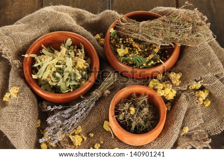 Medicinal Herbs in wooden bowls on bagging close-up - stock photo