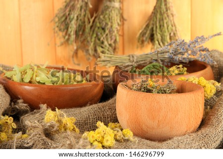 Medicinal Herbs in wooden bowls on bagging on table on wooden background - stock photo