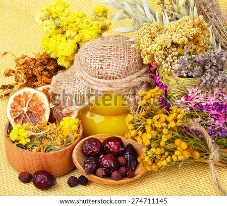 Medicinal herbs with honey, calendula, oats, immortelle flower, tansy herb, wild rose, dried lemon.  - stock photo