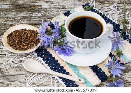 Medicinal plant chicory: flowers and ground roots. The roots of the plants are used as a substitute for coffee. Drink from chicory in a cup on the old wooden table. Rustic style, selective focus