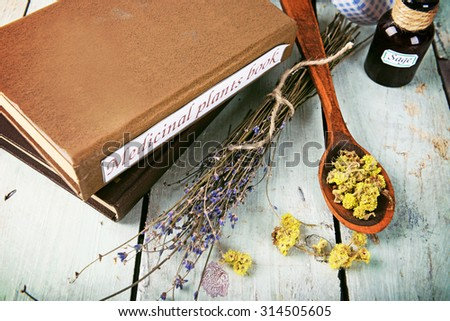 Medicinal plants book with dried herbs on table close up - stock photo