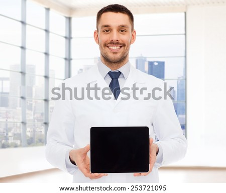 medicine, advertisement and people concept - smiling male doctor showing tablet pc computer blank screen over white room background - stock photo