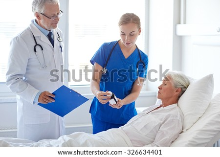 medicine, age, health care and people concept - doctor and nurse showing medicine to senior woman at hospital ward - stock photo