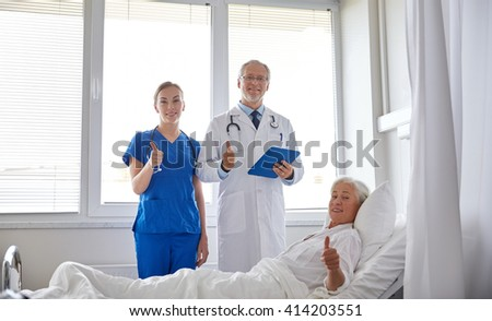 medicine, age, health care and people concept - doctor and nurse with tablet pc computer visiting senior patient woman and showing thumbs up at hospital ward - stock photo
