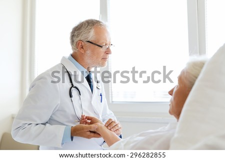 medicine, age, health care and people concept - doctor checking senior woman pulse at hospital ward - stock photo