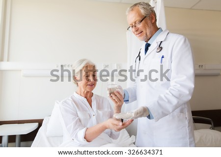 medicine, age, health care and people concept - doctor giving medication and water to senior woman at hospital ward - stock photo