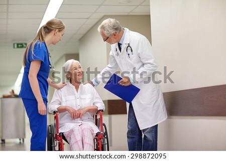 medicine, age, health care and people concept - doctor, nurse and senior woman patient in wheelchair at hospital corridor - stock photo