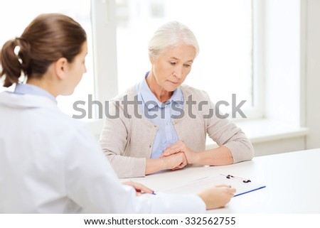 medicine, age, health care and people concept - doctor with clipboard and senior woman meeting at hospital - stock photo