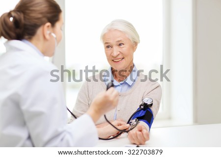 medicine, age, health care and people concept - doctor with tonometer checking happy senior woman blood pressure level at hospital - stock photo