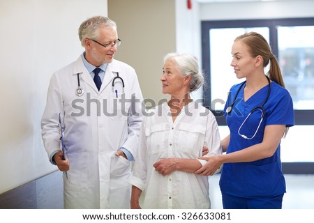 medicine, age, health care and people concept - male doctor with clipboard, young nurse and senior woman patient talking at hospital corridor - stock photo