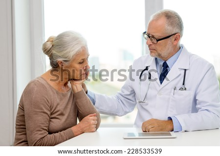 medicine, age, health care and people concept - senior woman and doctor with tablet pc computer meeting in medical office - stock photo